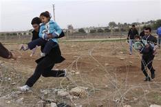 <p>Des Syriens fuyant des combats à la frontière avec la Turquie dans la ville de Ceylanpinar. Selon le Haut Commissariat des Nations unies pour les réfugiés, quelque 9.000 Syriens ont franchi cette frontière ces dernières 24 heures, ce qui porte à plus de 120.000 le nombre de réfugiés syriens en Turquie. /Photo prise le 9 novembre 2012/REUTERS</p>