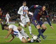 <p>David Villa du Barça (à droite) tenatant d'échapper au tacle de Manu Garcia d'Alaves, à Camp Nou. L'attaquant du FC Barcelone a porté son total de buts depuis le début de sa carrière à 301 en inscrivant un doublé lors du succès 3-1 des Catalans en 16es de finale Coupe du Roi. /Photo prise le 28 novembre 2012/REUTERS/Albert Gea</p>