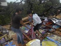 <p>Unas personas tratan de recuperar sus pertenencias tras la destrucción de su casa por el paso del tifón Bopha en Cagayan de Oro, Filipinas, dic 4 2012. El tifón más fuerte en azotar Filipinas este año arrasó el martes la isla sureña de Mindanao y la cifra de personas muertas o desaparecidas se eleva a 40, dijeron medios, luego de que la tormenta destruyera hogares y derribara redes de energía y comunicación. REUTERS/Stringer</p>