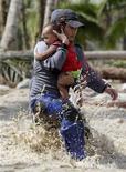 <p>Un socorrista transporta a un menor de un año de edad tras ser evacuado de la inundada zona de Nuevo Batan en Filipinas, dic 6 2012. Rescatistas encontraron el jueves en el sur Filipinas a unos pocos sobrevivientes del poderoso tifón Bopha, mientras buscaban en medio de espesas capas de lodo, viviendas destruidas y árboles caídos tras el desastre que dejó casi 400 muertos y cientos de desaparecidos. REUTERS/Erik De Castro</p>