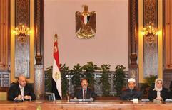<p>Mohamed Morsi (au centre), au palais présidentiel, au Caire. Le président égyptien a annulé samedi soir le décret qui élargissait ses prérogatives à l'origine d'une crise politique et de manifestations violentes en Egypte mais a refusé de reporter la date du référendum sur la nouvelle constitution comme le lui demandaient ses adversaires. /Photo prise le 8 décembre 2012/REUTERS/Présidence égyptienne</p>