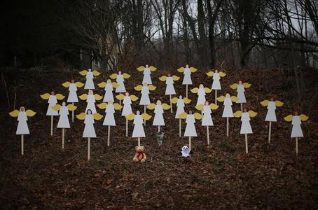 Twenty-seven wooden angel figures are seen placed in a wooded area beside a road near the Sandy Hook Elementary School for the victims of a school shooting in Newtown, Connecticut December 16, 2012. Twelve girls, eight boys and six adult women were killed in the shooting on Friday at the Sandy Hook Elementary School in Newtown. REUTERS/Mike Segar