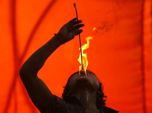 Manooj Sharma, a performer from Ambala, eats fire during a circus show at a fair in the troubled-torn city of Srinagar May 24, 2007.  REUTERS/Fayaz Kabli/Files