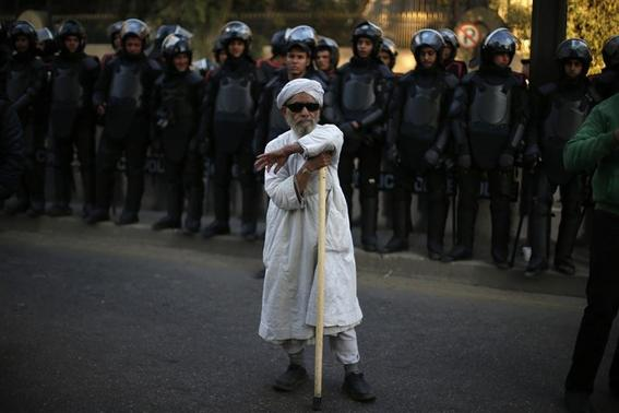 A protester takes part as members of Egyptian security forces stand guard during a protest against the French operation in Mali outside the French embassy in Cairo January 18, 2013. REUTERS/Suhaib Salem