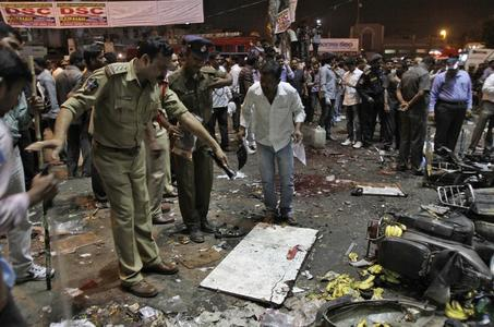 Police officers examine the site of an explosion at Dilsukh Nagar, in Hyderabad February 21, 2013. Two bombs placed on bicycles exploded in a crowded market-place in Hyderabad on Thursday, and the home minister said at least 11 people were killed and 50 wounded. REUTERS/Krishnendu Halder