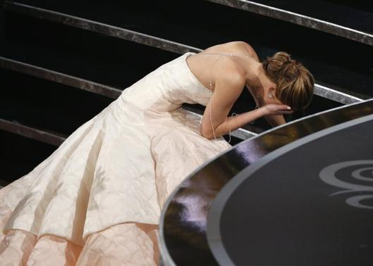 Actress Jennifer Lawrence falls as she walks up the steps to accept the award for best actress for her role in 'Silver Linings Playbook' at the 85th Academy Awards in Hollywood, California February 24, 2013.     REUTERS/Mario Anzuoni