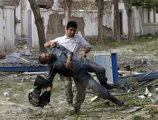 A wounded Afghan policeman is carried away from the site of an explosion in Kabul after Taliban militants launched a coordinated attack on a U.N. compound in the center of the Afghan capital, May 24, 2013. REUTERS-Omar Sobhani