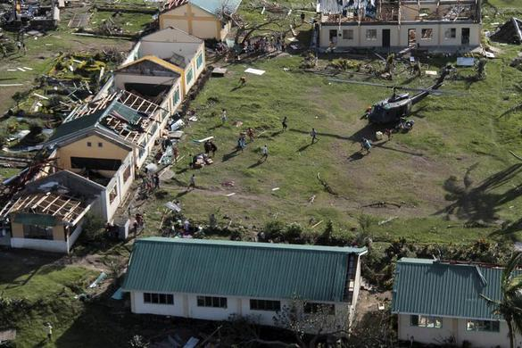 An aerial view shows damaged structures as residents unload relief goods from a helicopter after Typhoon Haiyan hit a village in Panay island in northern Iloilo Province, central Philippines November 9, 2013. REUTERS-Leo Solinap