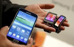 Samsung Electronics a dévoilé lundi soir la nouvelle version de son smartphone vedette, le Galaxy S5, ainsi qu'un nouveau bracelet et une nouvelle montre connectés à internet, cherchant ainsi à déplacer la bataille sur l'innovation sur le terrain des objets à porter sur soi. /Photo prise le 23 février 2014/REUTERS/Albert Gea