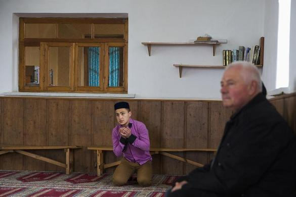 A Crimean Tatar prays in the Khan Chair mosque in Bakhchisaray, near Simferopol March 7, 2014. REUTERS-Thomas Peter