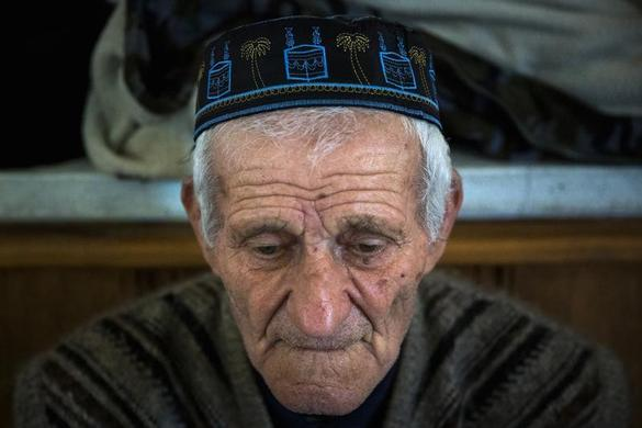 A Crimean Tatar sits in the Khan Chair mosque after Friday prayers in Bakhchisaray, near Simferopol March 7, 2014. Earlier this month, Tatars of Ukraine's Crimea came out in their thousands, chanting Allahu Akbar in a show of loyalty to the new authorities in Kiev and opposition to separatist demands by the region's Russian ethnic majority. But now, with Moscow's military forces having unexpectedly seized control, the indigenous Muslim people of the isolated Black Sea peninsula have all but vanished from the public square, keeping their heads down to avoid being sucked into war. REUTERS-Thomas Peter
