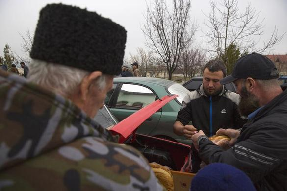 Crimean Tatars buy bread after praying in the Khan Chair mosque in Bakhchisaray, near Simferopol March 7, 2014. REUTERS-Thomas Peter