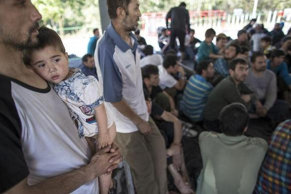 A suspected Uighur from China's troubled far-western region of Xinjiang, holds his son at a temporally shelter after they were detained at the immigration regional headquarters near the Thailand-Malaysia border in Hat Yai, Songkla March 14, 2014. REUTERS-Athit Perawongmetha