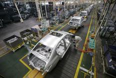 Dongfeng Motor, dont le partenariat stratégique avec PSA Peugeot Citroën et l'Etat français a été formalisé mercredi, fait état d'un bénéfice 2013 supérieur aux attentes et en hausse de 16% à 10,53 milliards de yuan (1,24 milliard d'euros) grâce au rebond des ventes d'automobiles de ses co-entreprises avec des constructeurs japonais. /Photo prise le 13 février 2014/REUTERS/Darley Shen