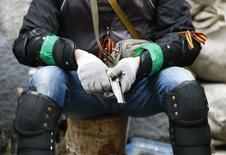 Вооруженный мужчина у здания милиции в Славянске, Украина 13 апреля 2014 года. Объявленный властями Украины крайний срок добровольного разоружения пророссийских повстанцев миновал, но признаков подчинения этому требованию не наблюдается, сообщил корреспондент Рейтер с места событий. REUTERS/Gleb Garanich