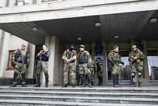 Пророссийские активисты с оружием у мэрии Славянска на востоке Украины 14 апреля 2014 года.  Киев не стал атаковать промосковских сепаратистов на востоке страны по истечении ультиматума в понедельник и согласился с их идеей выяснить отношение граждан к государственному устройству Украины путём референдума, но предложил совместить его с президентскими выборами 25 мая.