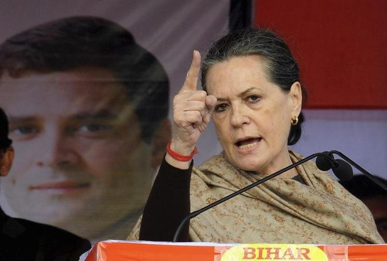 Chief of ruling Congress party Sonia Gandhi addresses a gathering next to a portrait of her son and lawmaker Rahul Gandhi during the foundation laying stone ceremony of a proposed university campus in Bihar January 30, 2014. REUTERS/Krishna Murari Kishan/Files