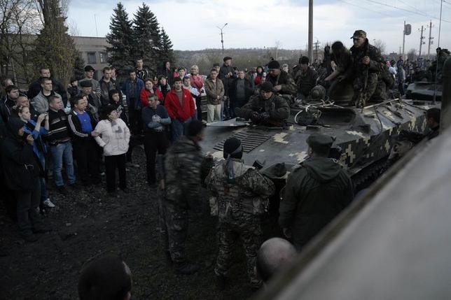 An armed man (C, bottom, front), believed to be pro-Russian as he wears a black and orange ribbon of St. George - a symbol widely associated with pro-Russian protests in Ukraine, talks to Ukrainian servicemen on an armoured personnel carrier, while local residents surround them, in Kramatorsk, April 16, 2014. REUTERS/Maks Levin