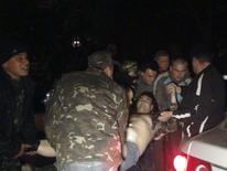 Люди несут мужчину, раненного в столкновениях на территории воинской части в Мариуполе 16 апреля 2014 года. Украинские силовики застрелили троих из нескольких сотен напавших на воинскую часть в Мариуполе на востоке страны, где Киев начал войсковую операцию против промосковских сепаратистов, сообщил глава МВД в своём фейсбуке в четверг, добавив, что столкновение продолжается. REUTERS/Stringer