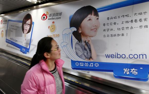 A woman looks at a Weibo advertisement as she rides an elevator inside a subway station in Beijing February 25, 2012. REUTERS/China Daily/Files