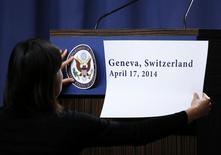 Член американской делегации прикрепляет логотип Госдепартамента США к трибуне перед выступлением Джона Керри после переговоров в Женеве 17 апреля 2014 года. Признаки дипломатического компромисса в Женеве взвинтили цены на российские акции в начале торгов пятницы, и биржевые индексы прибавили более 2 процентов. REUTERS/Denis Balibouse