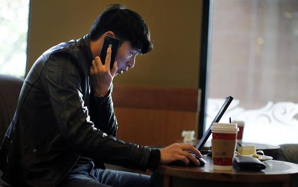 A man talks on the phone as he surfs the internet on his laptop at a local coffee shop in downtown Shanghai November 28, 2013. REUTERS/Carlos Barria/Files