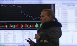 Женщина проходит мимо табло на Московской бирже 14 марта 2014 года. Минфин РФ не исключает отрицательного значения динамики ВВП в одном из кварталов 2014 года, ждет всплеска инфляции в мае-июне с последующим замедлением до менее 6 процентов и ожидает по итогам года отток капитала на уровне $70-80 миллиардов, сказал на брифинге директор департамента долгосрочного стратегического планирования Минфина Максим Орешкин. REUTERS/Maxim Shemetov