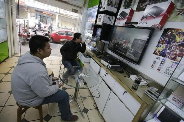 A man plays video game at a store selling video game consoles in Wuhan, Hubei province, January 9, 2014. REUTERS/Darley Shen/Files