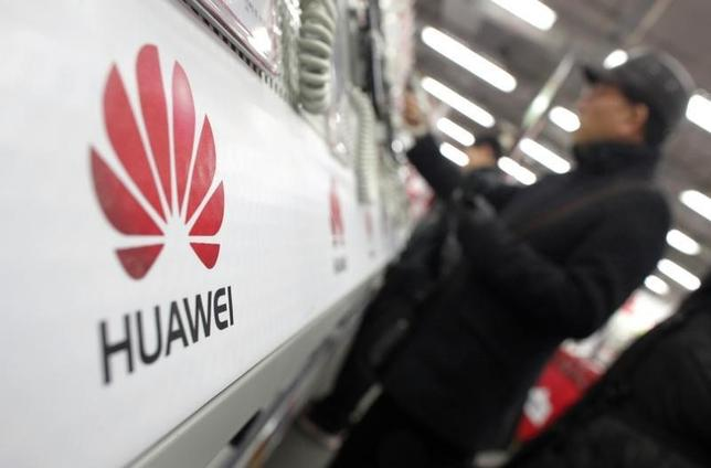 A man looks at a Huawei mobile phone as he shops at an electronic market in Shanghai January 22, 2013. REUTERS/Carlos Barria/Files