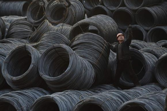 A labourer works on piles of steel coils in Taiyuan, Shanxi province, February 22, 2013. China's factory activity shrank for the fourth straight month in April, signalling economic weakness into the second quarter, a preliminary survey showed on April 23, 2014, although the pace of decline eased helped by policy steps to arrest the slowdown. Picture taken February 22, 2013. REUTERS/Jon Woo (CHINA - Tags: BUSINESS INDUSTRIAL) CHINA OUT. NO COMMERCIAL OR EDITORIAL SALES IN CHINA - RTR3MA1R
