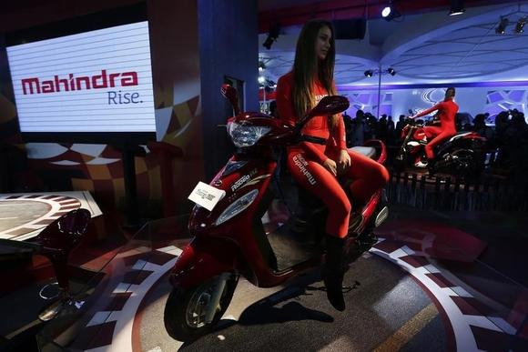 A model sits on a Rodeo RZ scooter at the Mahindra and Mahindra pavilion during the Indian Auto Expo in Greater Noida, on the outskirts of New Delhi February 6, 2014. REUTERS/Adnan Abidi/Files