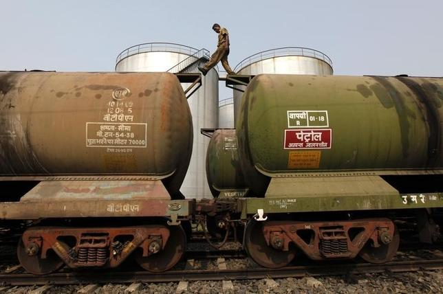 A worker walks atop a tanker wagon to check the freight level at an oil terminal on the outskirts of Kolkata November 27, 2013. REUTERS/Rupak De Chowdhuri/Files