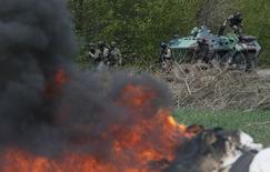 Украинские военные у блокпоста близ Славянска 24 апреля 2014 года. Украинские военные при поддержке легкой бронетехники взяли под контроль блокпост сепаратистов к северу от Славянска после того, как пророссийские повстанцы покинули позиции, передал корреспондент Рейтер с места событий. REUTERS/Gleb Garanich