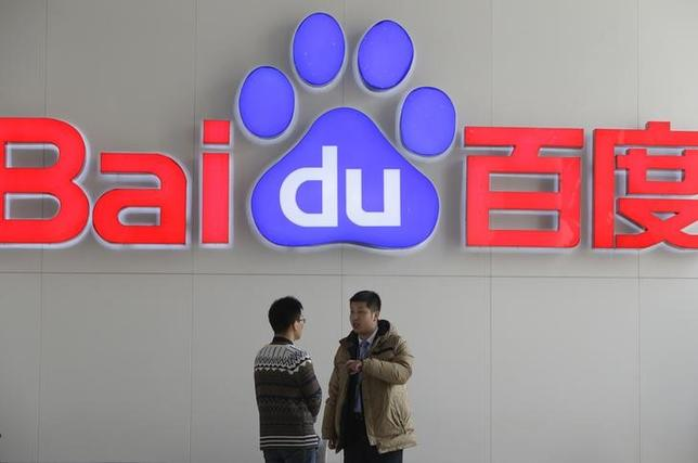 People talk in front of a Baidu's company logo at Baidu's headquarters in Beijing January 16, 2014. REUTERS/Jason Lee/Files