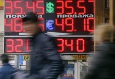 Люди проходят мимо пункта обмена валют в Москве 3 апреля 2014 года. Рубль отметился на недельных минимумах к бивалютной корзине и её компонентам при открытии биржевых торгов пятницы в ответ на понижение суверенного рейтинга России агентством S&P и в условиях эскалации ситуации на востоке Украины. REUTERS/Maxim Shemetov