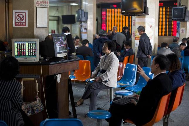 Investors look at computer screens showing stock information at a brokerage house in Shanghai, April 14, 2014. REUTERS/Aly Song