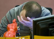 Трейдер на торгах ММВБ в Москве 28 ноября 2008 года. Торги российскими акциями начались в понедельник с резкого снижения индексов на фоне угрозы США и ЕС расширить список санкций в отношении РФ. REUTERS/Sergei Karpukhin