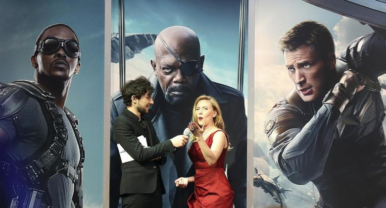 Actress Scarlett Johansson (R) gestures to the crowd during an interview at the UK premiere of ''Captain America: The Winter Soldier: at Shepherds Bush in London, March  20, 2014. REUTERS/Paul Hackett