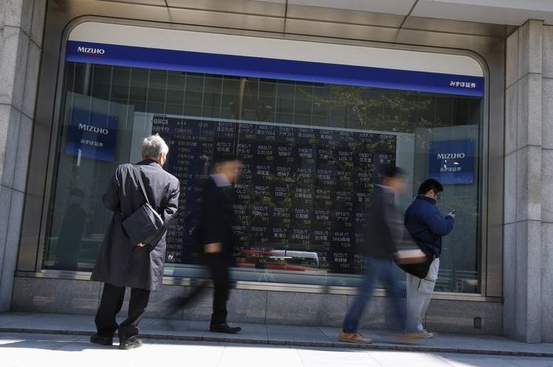 A man (L) looks at a stock quotation board outside a brokerage in Tokyo April 14, 2014. REUTERS/Issei Kato