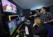 The Simpsons show editor Mike Bridge (L), executive producer Matt Selman (R) and co-executive producer Brian Kelley look at an upcoming Lego episode at the editing bay in 20th Century Fox Studios in Los Angeles, California April 22, 2014. REUTERS/Kevork Djansezian