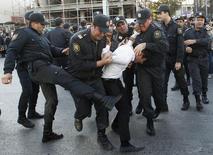 Полиция задерживает участника акции протеста в Баку 12 октября 2013 года. Уполномоченный по правам человека в Совете Европы призвал богатый нефтью Азербайджан гарантировать право граждан на свободу собраний и выражения мнений и прекратить давление на правозащитников.  REUTERS/David Mdzinarishvili