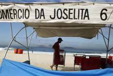 A man arranges beach chairs at his stall at Ipanema beach in Rio de Janeiro April 29, 2014.   REUTERS/Pilar Olivares