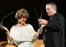Israeli film director Assi Dayan recieves his trophy from actress Joan Collins during the closing ceremony of the XIX Mediterranean Film Festival in Valencia October 20.