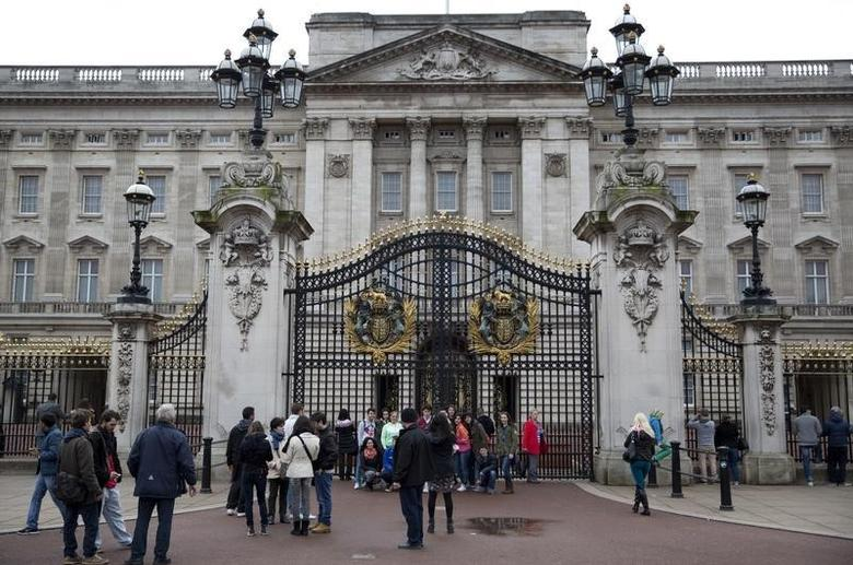 Tourists pose for photographs in front of Buckingham Palace in central London April 6, 2014.  Reuters/Neil Hall