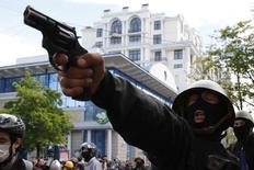 Пророссийский активист целится из пистолета в прокиевских протестующих во время столкновений на улицах Одессы, 2 мая 2014 года. Украинская милиция сообщила о более 30 погибших в Одессе в результате пожара в Доме профсоюзов, возникшем после столкновений пророссийских и проукраинских активистов в центре города, унесших жизни как минимум четырех. REUTERS/Yevgeny Volokin
