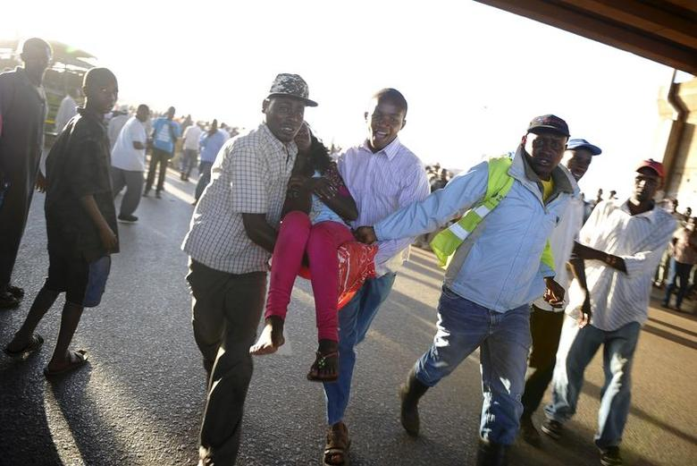 Residents assist an injured passenger from the scene of a bus explosion along the Thika super-highway in Kenya's capital Nairobi, May 4, 2014. REUTERS/David Kamau