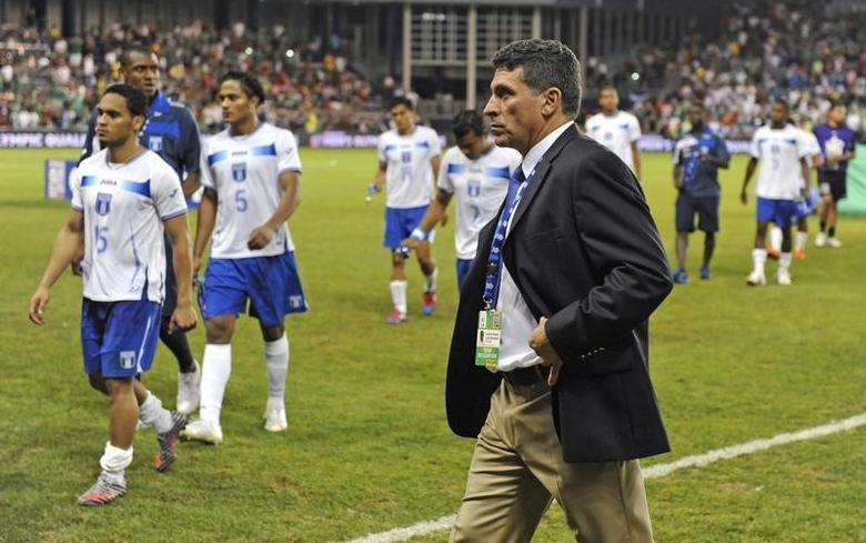 Honduras' coach Luis Fernando Suarez and his team walk off the field after Mexico's overtime win in the CONCACAF Olympic qualifying finals soccer match in Kansas City, Kansas April 2, 2012. REUTERS/Dave Kaup