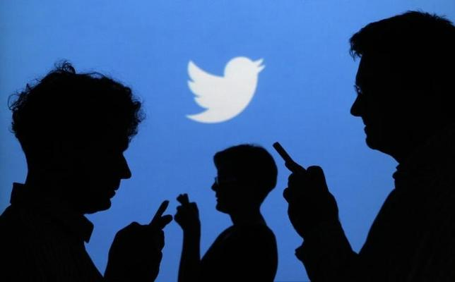 People holding mobile phones are silhouetted against a backdrop projected with the Twitter logo in this illustration picture taken in  Warsaw September 27, 2013. REUTERS/Kacper Pempel/Files