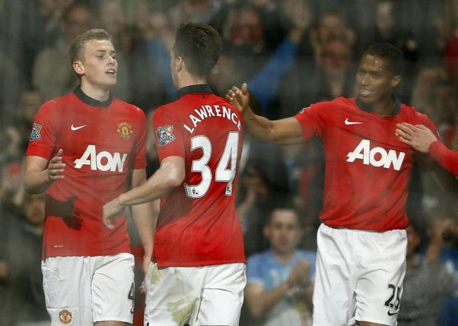 Manchester United's James Wilson (L) celebrates with teammates Tom Lawrence (C) and Antonio Valencia after scoring a second goal against Hull City during their English Premier League soccer match at Old Trafford in Manchester, northern England May 6, 2014.    REUTERS/Darren Staples