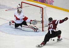 Latvia's Miks Indrasis (R) attempts a shot on Canada's goalie Carey Price during the second period of their men's quarter-finals ice hockey game at the Sochi 2014 Winter Olympic Games February 19, 2014. REUTERS/Jim Young